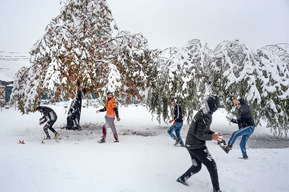 Youngsters play with snow at a park in Srinagar on Thursday. Heavy snowfall across Kashmir on Thursday cut off the Valley from the rest of the country. The Jammu-Srinagar National Highway was closed for traffic while all flights connecting Srinagar were cancelled