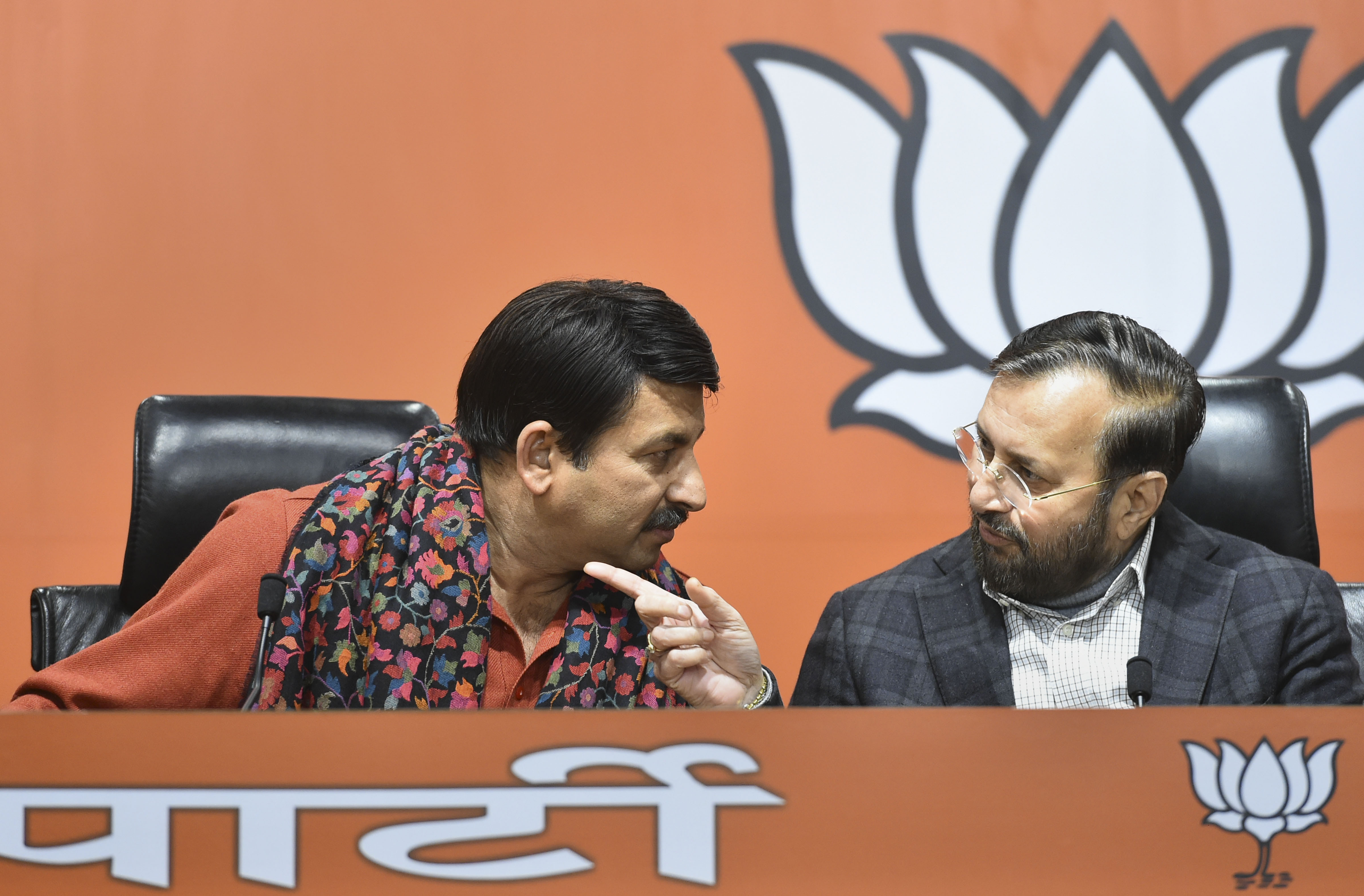 Delhi BJP unit president Manoj Tiwari interacts with Union minister Prakash Javadekar during the release of BJP's first list of 57 candidates for Delhi Assembly polls, at BJP headquarters in New Delhi, Friday, January 17, 2020.