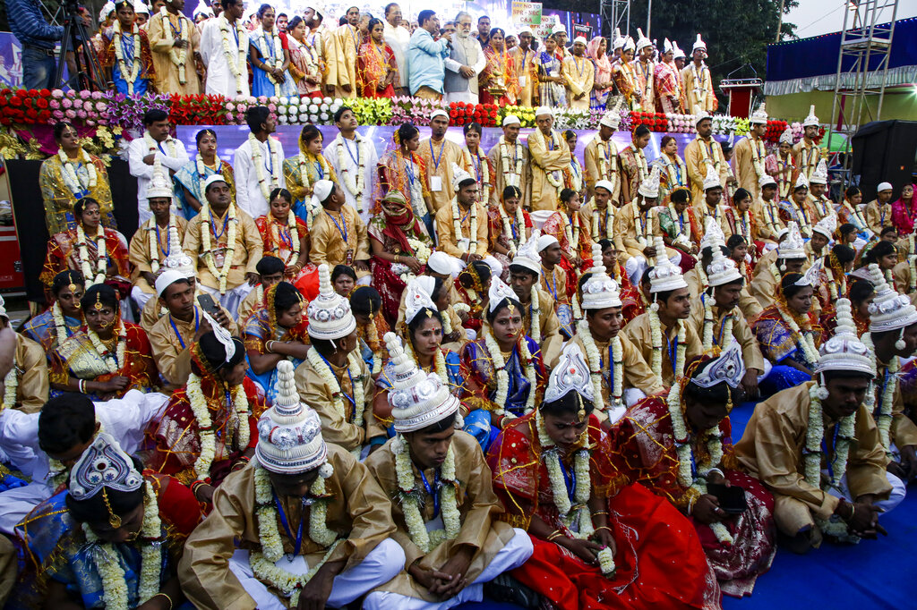 Brides and grooms sit for a group photograph during a mass marriage ceremony for eighty five couples of various religions in Kolkata