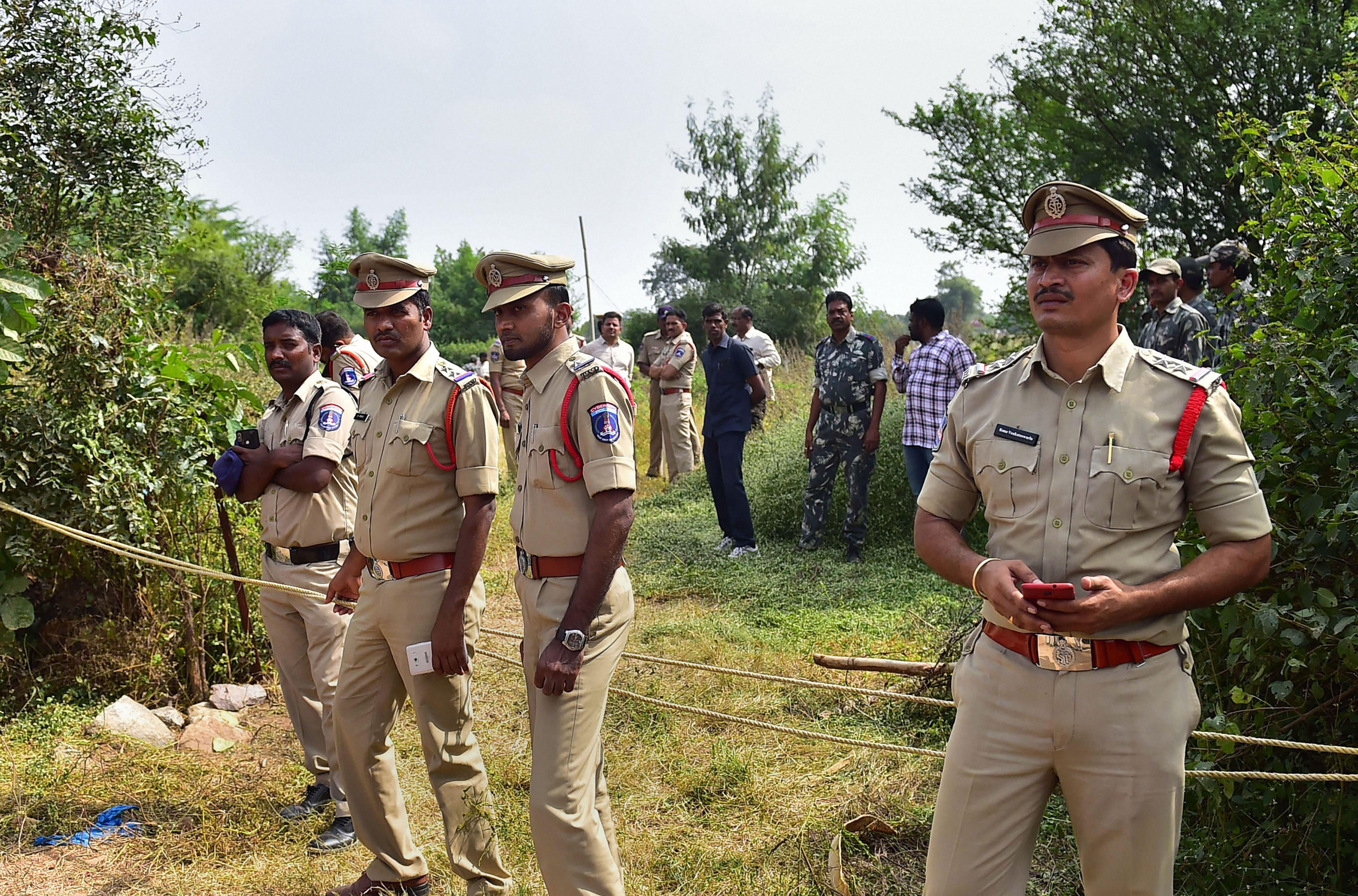 Policemen stand guard the area where four accused in the rape and murder case of a woman veterinarian were shot dead by police, at Shadnagar of Ranga Reddy district in Hyderabad, Friday, Dec. 6, 2019