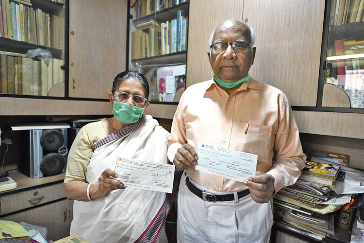 Arun and Chitralekha Bhattacharyya with the cheques on Monday.