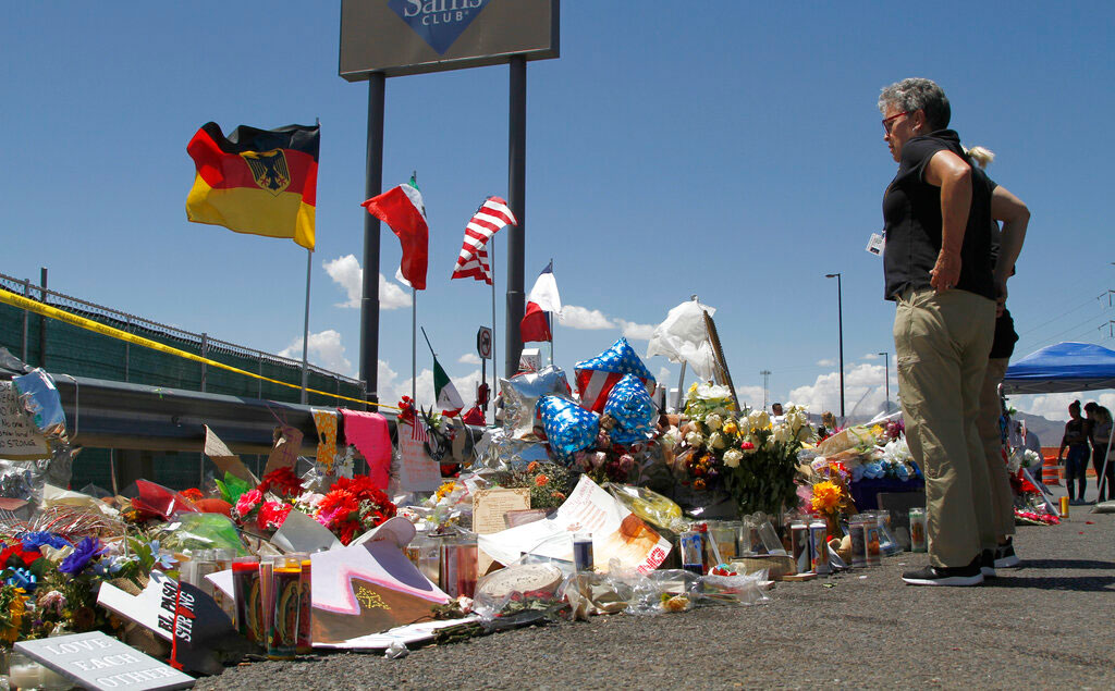 In this August 12, 2019, picture, mourners visit the makeshift memorial near the Walmart in El Paso, Texas, where 22 people were killed in a mass shooting that police are investigating as a terrorist attack targeting Latinos.