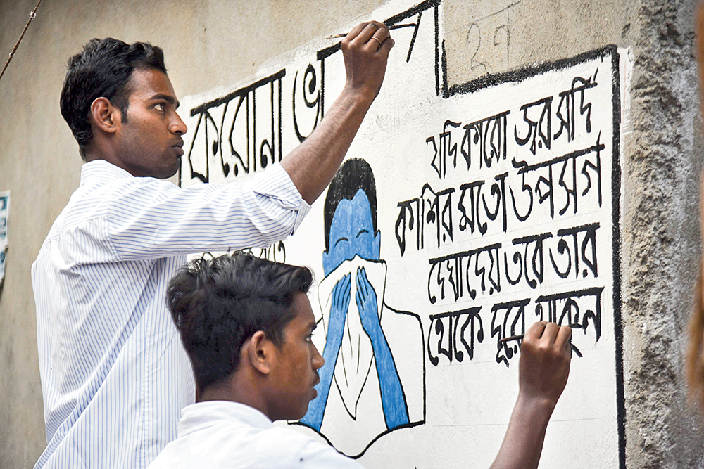 Prayasam workers write messages on walls to protect against novel coronavirus in communities