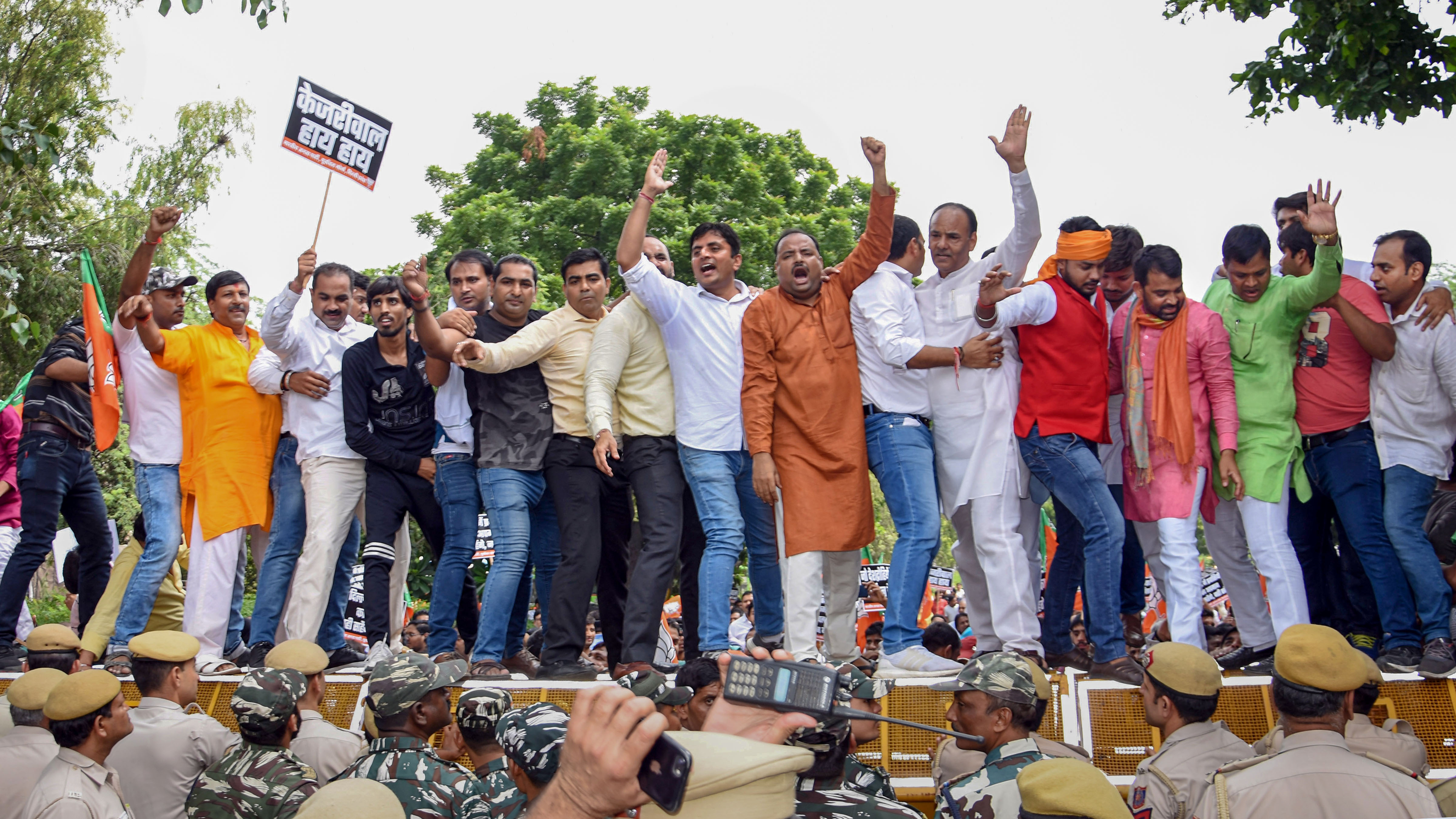 BJP workers stand on police barricades during a protest near the residence of Delhi chief minister Arvind Kejriwal over his NRC remark against party chief Manoj Tiwari, in New Delhi, Thursday, September 26, 2019
