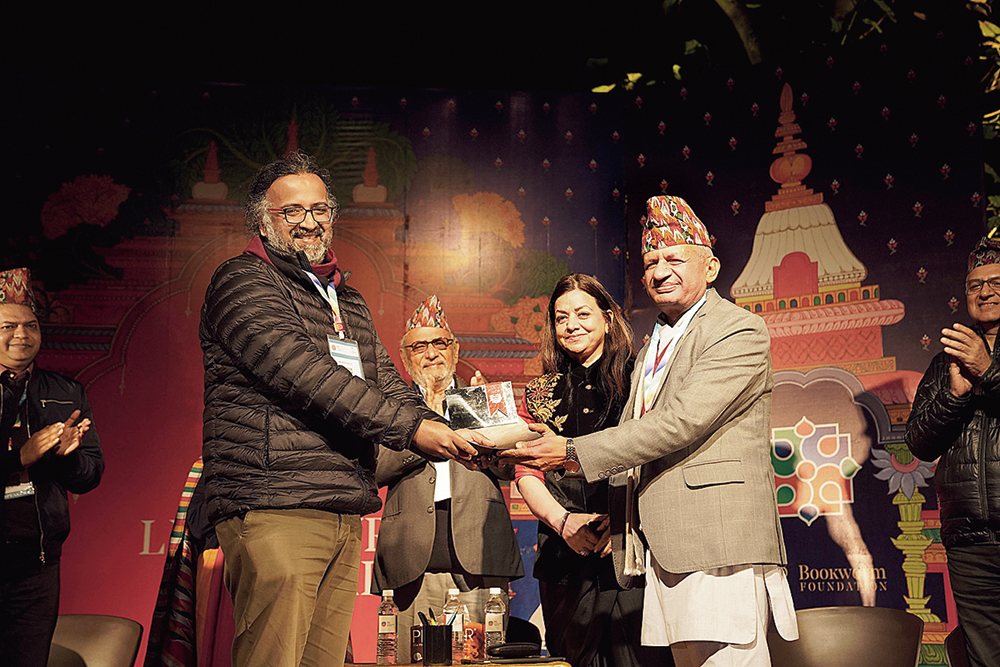 Amitabha Bagchi (left), winner of the DSC Prize 2019, receives the trophy from Pradeep Gyawali, minister for foreign affairs, Nepal (right) and Surina Narula, co-founder, DSC Prize, (second from right) to applause from Harish Trivedi