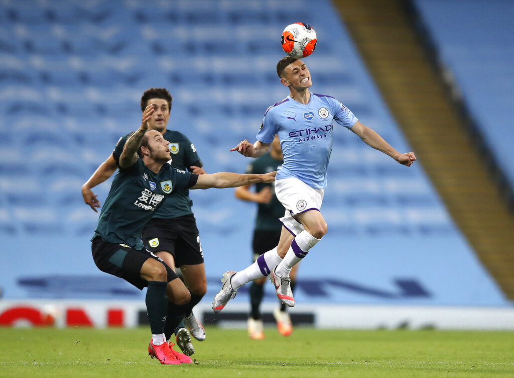 Manchester City's Phil Foden heads the ball away from Josh Brownhill of Burnley during their Premier League match at the Etihad Stadium on Monday.