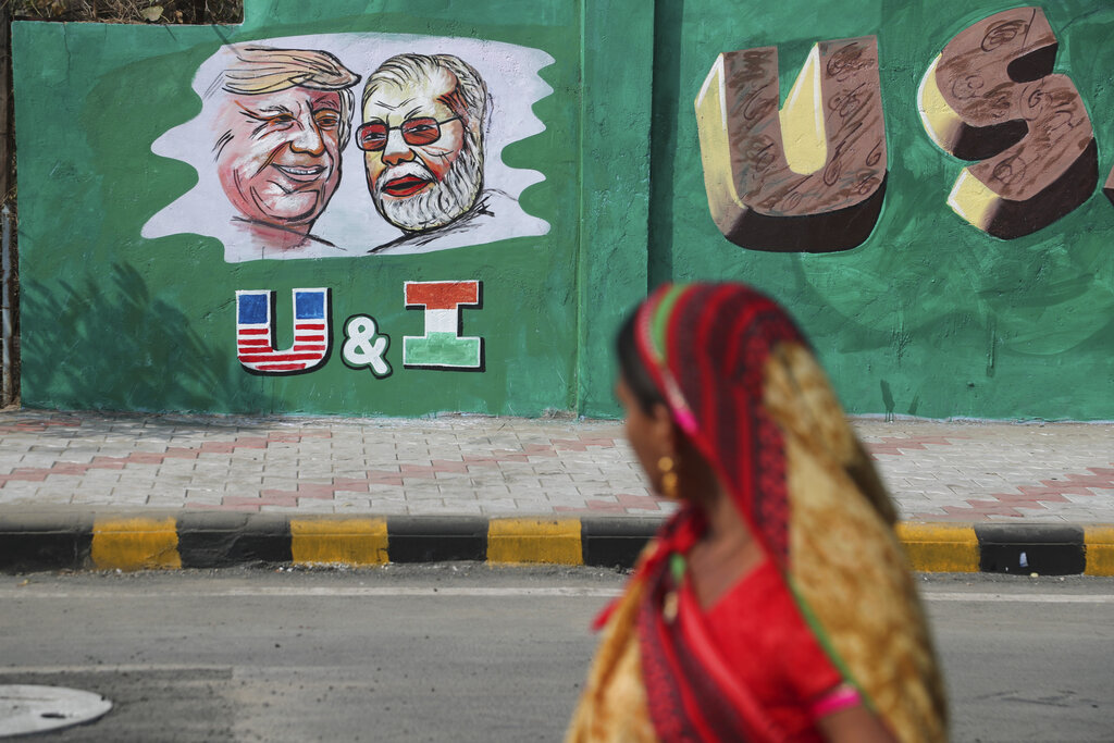 An Indian woman looks at a wall painted with portraits of U.S. President Donald Trump and Indian Prime Minister Narendra Modi ahead of Trump's visit, in Ahmadabad, on Tuesday