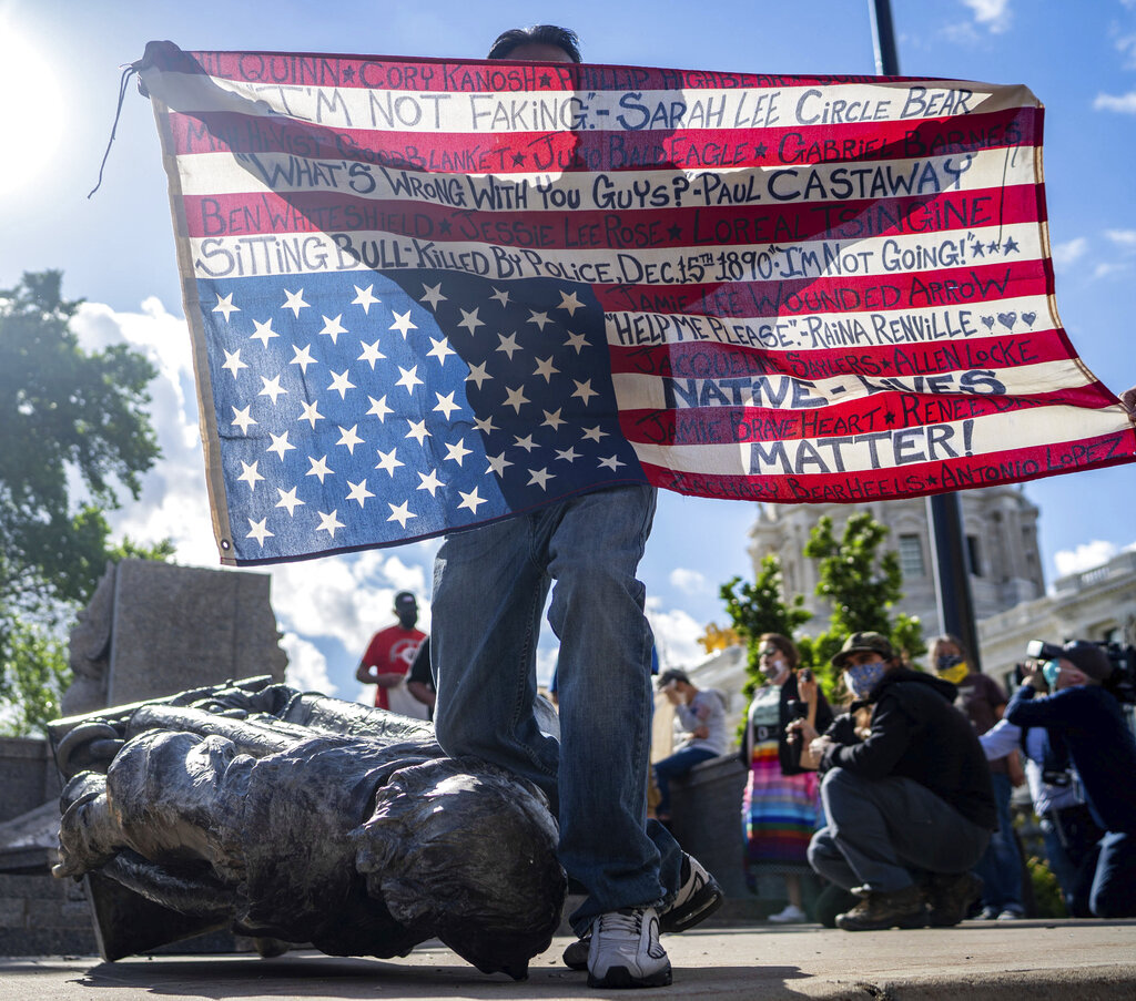 Gabriel Black Elk, who is Lakota, kneels on the neck of a fallen statue of Christopher Columbus and holds an American flag with the names of Native Americans killed by police, at the Minnesota state Capitol in St. Paul, Minn., Wednesday, June 10, 2020.