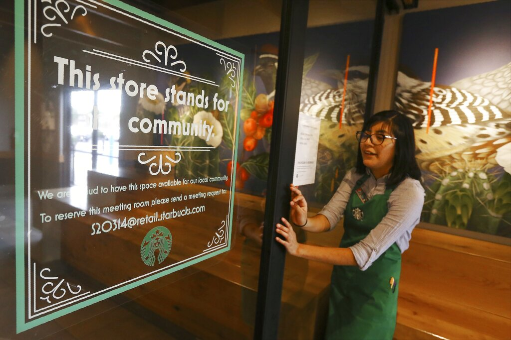Belith Ariza, a barista trainer at Starbucks, opens the doors to the community meeting space at a local Starbucks Community Store, in Phoenix