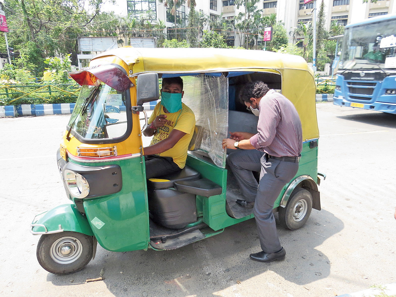 A commuter gets into an autorickshaw with a new plastic partition at the Sports Authority of India gate.