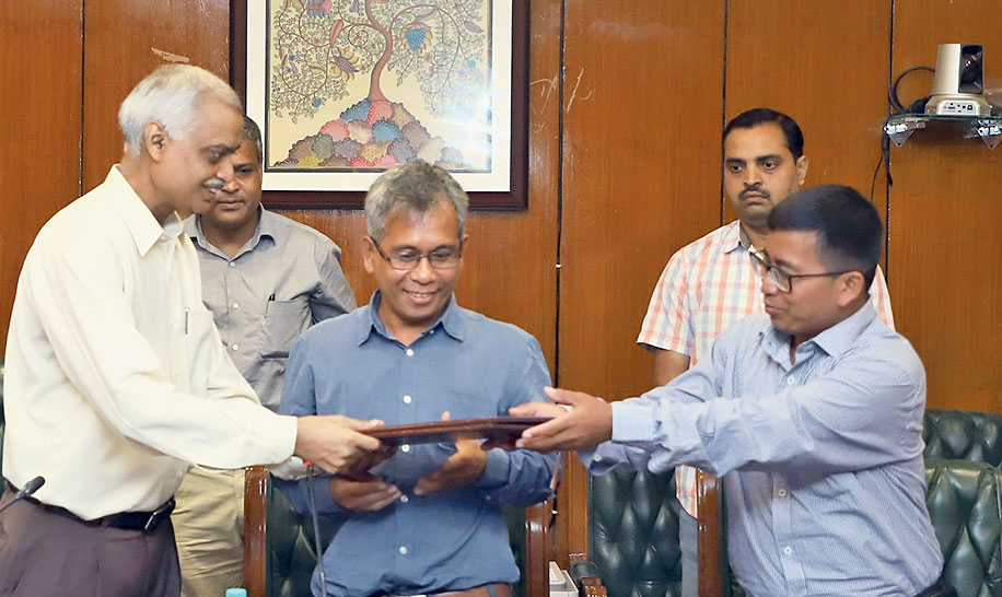 Satyendra Garg exchanges files with the NLFT-SD representatives after signing the memorandum of settlement in New Delhi on Saturday.