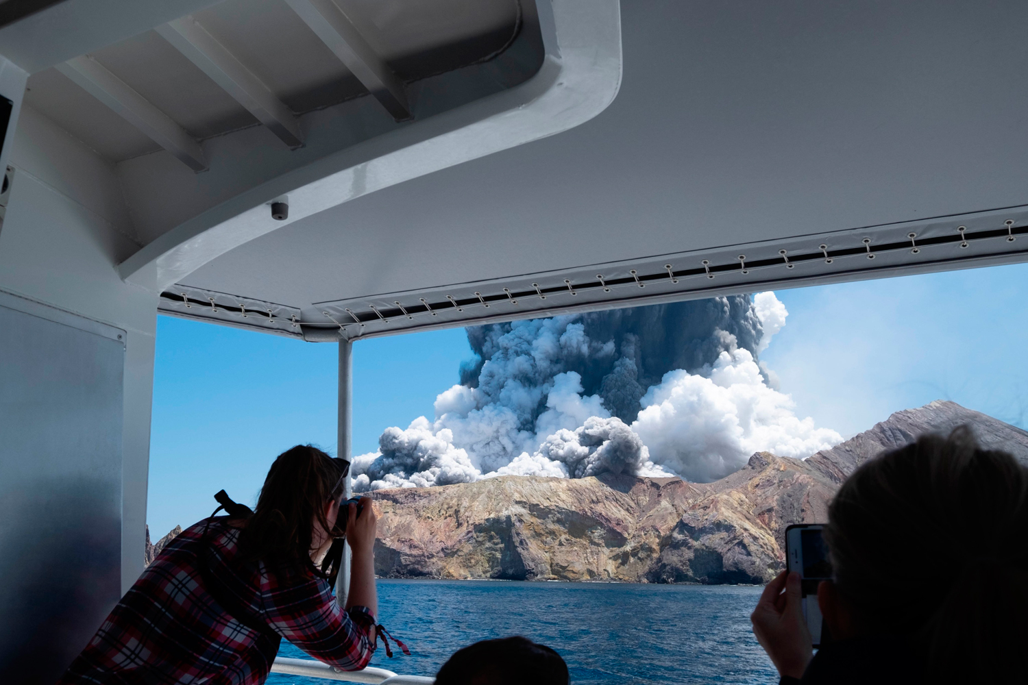 Tourists on a boat look at the eruption of the volcano on White Island, New Zealand