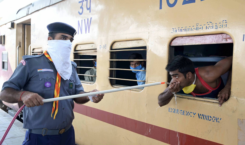 A cadet of Scouts & Guides provides drinking water to the migrants traveling in a Shramik Special train to their native places, during ongoing Covid-19 lockdown, at Prayagraj Railway Station,Thursday, May 28, 2020.