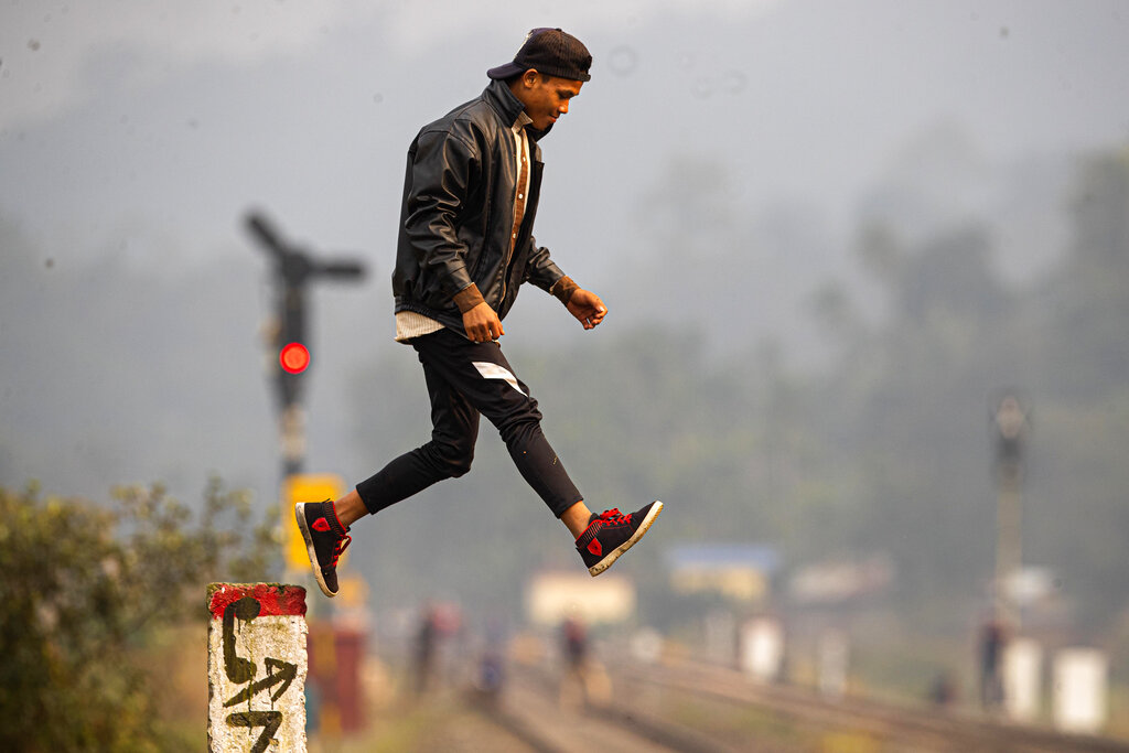 A boy jumps from a pole near a railway track after watching a herd of wild elephants graze in a forested area at Panbari village, on the outskirts of Gauhati, India, Tuesday