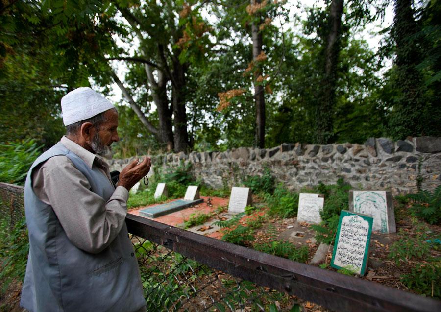 A Kashmiri man prays near an unmarked grave that reads,