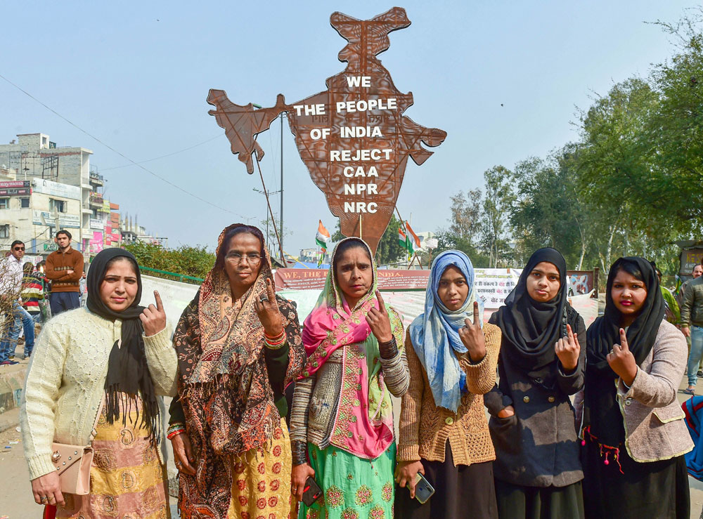 Protesters show their ink-marked fingers after casting votes for the Delhi Assembly elections, near the site of their peaceful agitation against the Citizenship Act, in Shaheen Bagh, New Delhi, on Saturday