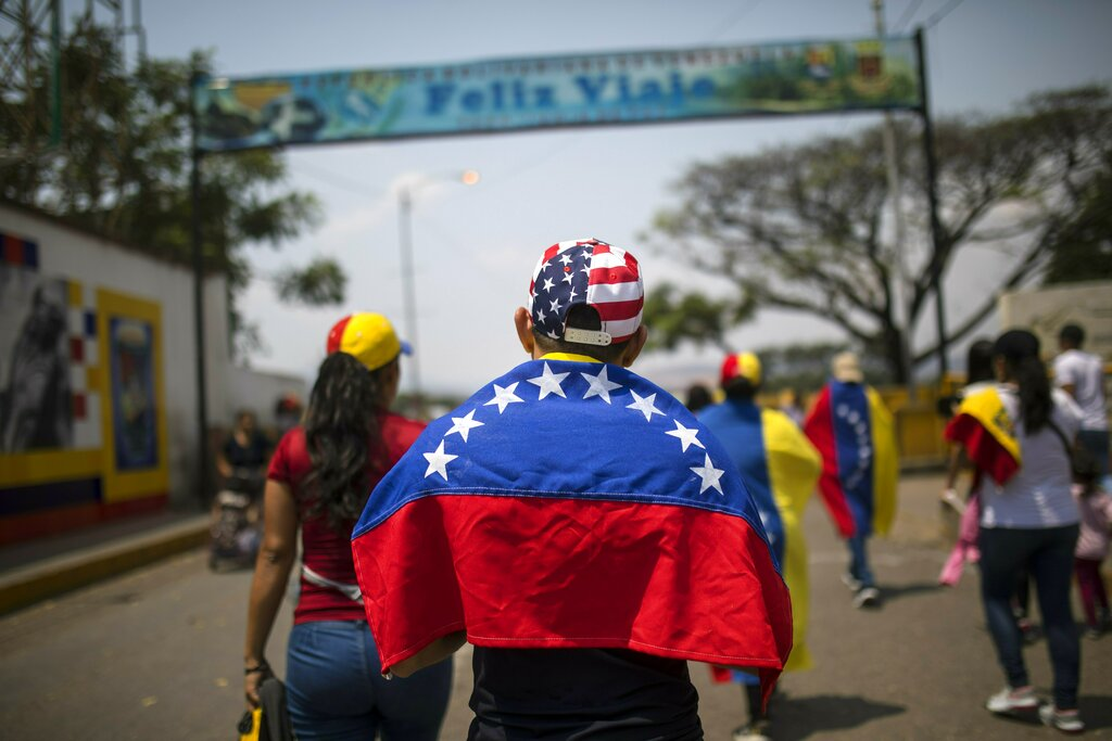 Larry Rios, bearing a Venezuelan national flag on his shoulders and sporting a stars-and-stripes cap, makes his way to the Venezuela Aid Live concert on the Colombian side of the Las Tienditas bridge, which connects to Venezuela, in Cucuta on Friday.