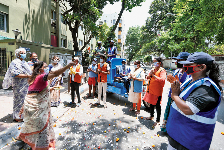 Gratitude: Residents of Mandeville Gardens shower flowers on Calcutta Municipal Corporation health workers in their ward on Saturday.