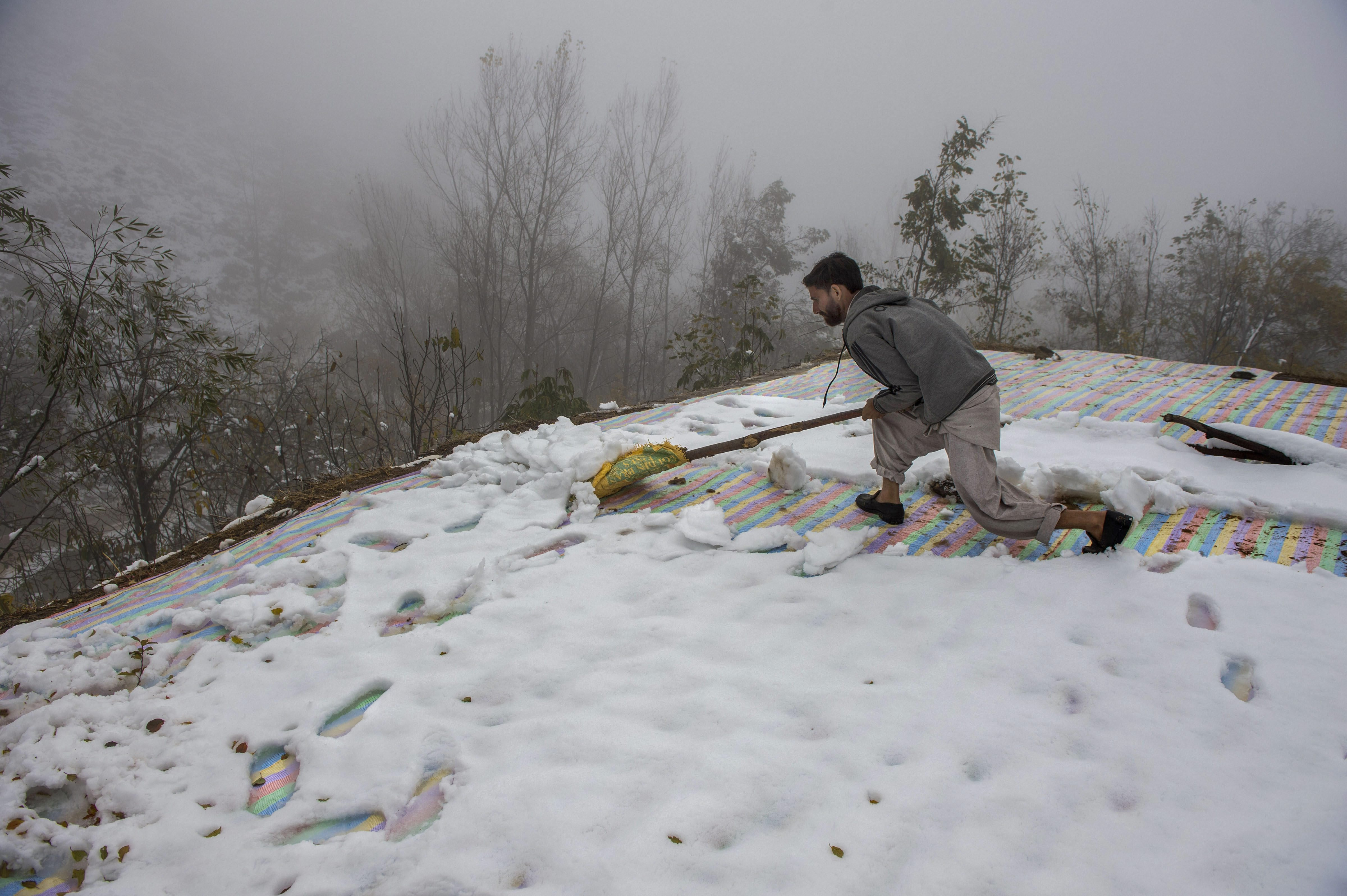 A man clears snow from the roof of his house on the outskirts of Srinagar.