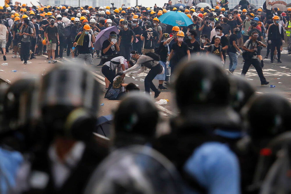Protesters help a fallen person after clashing with riot police during a massive demonstration outside the Legislative Council in Hong Kong on Wednesday