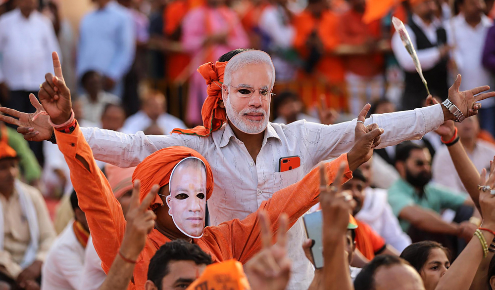 BJP supporters wear masks of Prime Minister Narendra Modi and Uttar Pradesh Chief Minister Yogi Adityanath as BJP President Amit Shah addresses an election campaign for the Lok Sabha Elections 2019, in Prayagraj (Allahabad), Monday, April 29, 2019.