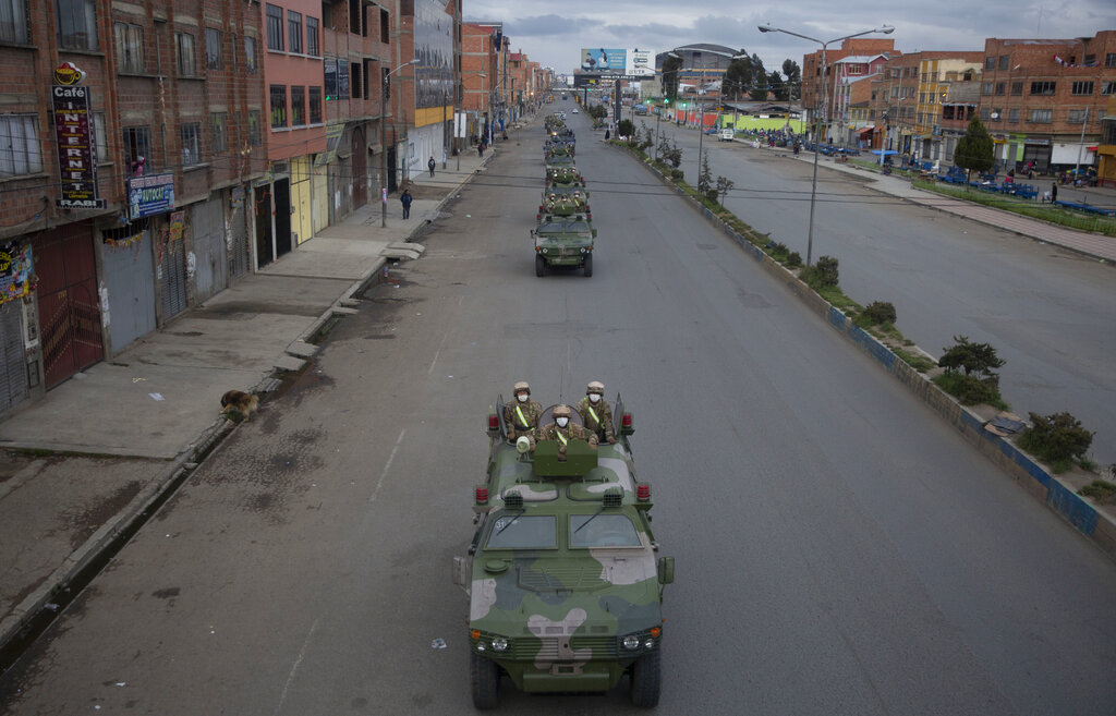 Military armored vehicles patrol the streets during a quarantine in El Alto, Bolivia, Friday, March 20, 2020. Authorities have decreed a quarantine from 5pm to 5am in an attempt to stop the spread of the new coronavirus.