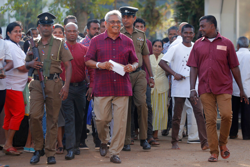 Gotabaya Rajapaksa (centre) leaves a polling station after casting his vote in Embuldeniya, on the outskirts of Colombo, on Saturday