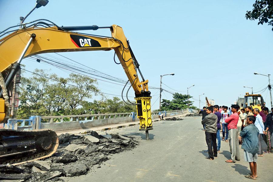 A machine digs up bitumen on the Tallah bridge on Sunday