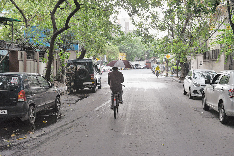 A man  cycles down a road in Ballygunge in the rain on Tuesday.