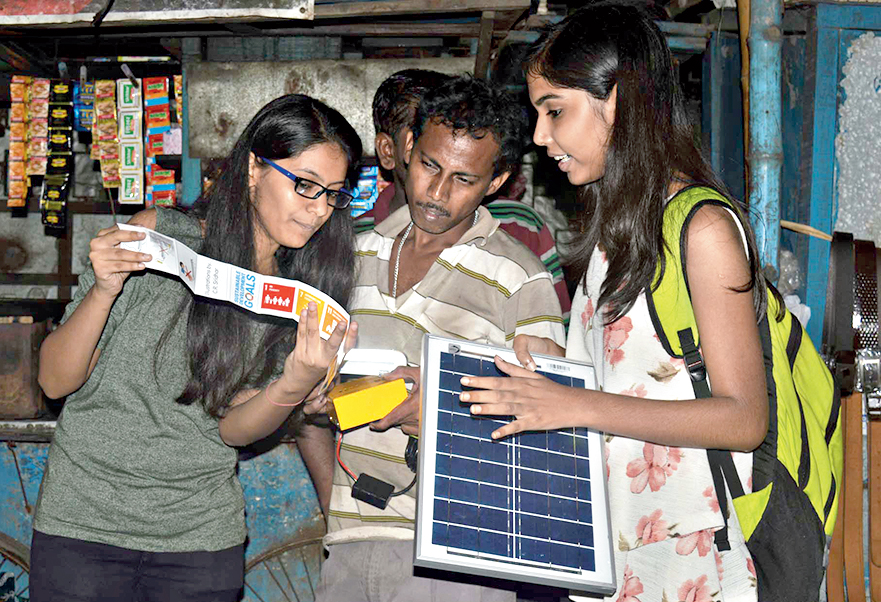 Techno India students show the manual on using and recharging the solar lamp to Dilip Burman, a street vendor of Ultadanga.