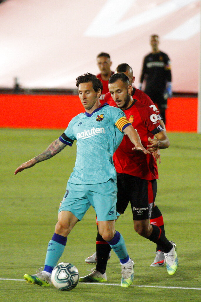 Barcelona's Lionel Messi  vies for the ball with Mallorca's Joan Sastre during the La Liga match between Mallorca and FC Barcelona