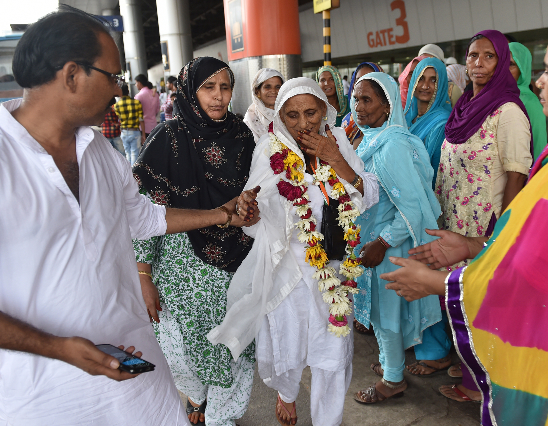 A pilgrim leaves for Haj with a male family member in 2016