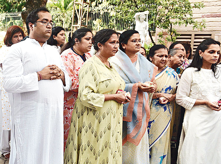 Grandson Amritanshu (far left) were among the mourners