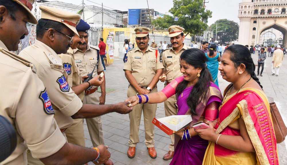 Women offer sweet to policemen as they commend the Hyderabad Police for its action against the four accused in the gang rape and murder of a 25-year-old veterinarian, in Hyderabad, Friday, December 6, 2019.