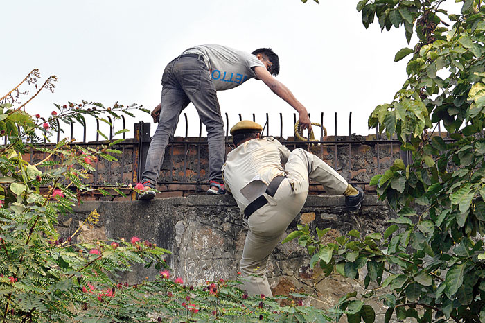 A student tries to scale the wall and enter the AICTE premises and a policeman strives to thwart him. The policeman eventually succeeded.