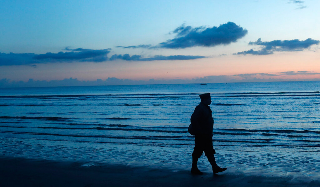 A World War II re-enactor stands on Omaha Beach, in Normandy, France, at dawn on Thursday, June 6, 2019 during commemorations of the 75th anniversary of D-Day.