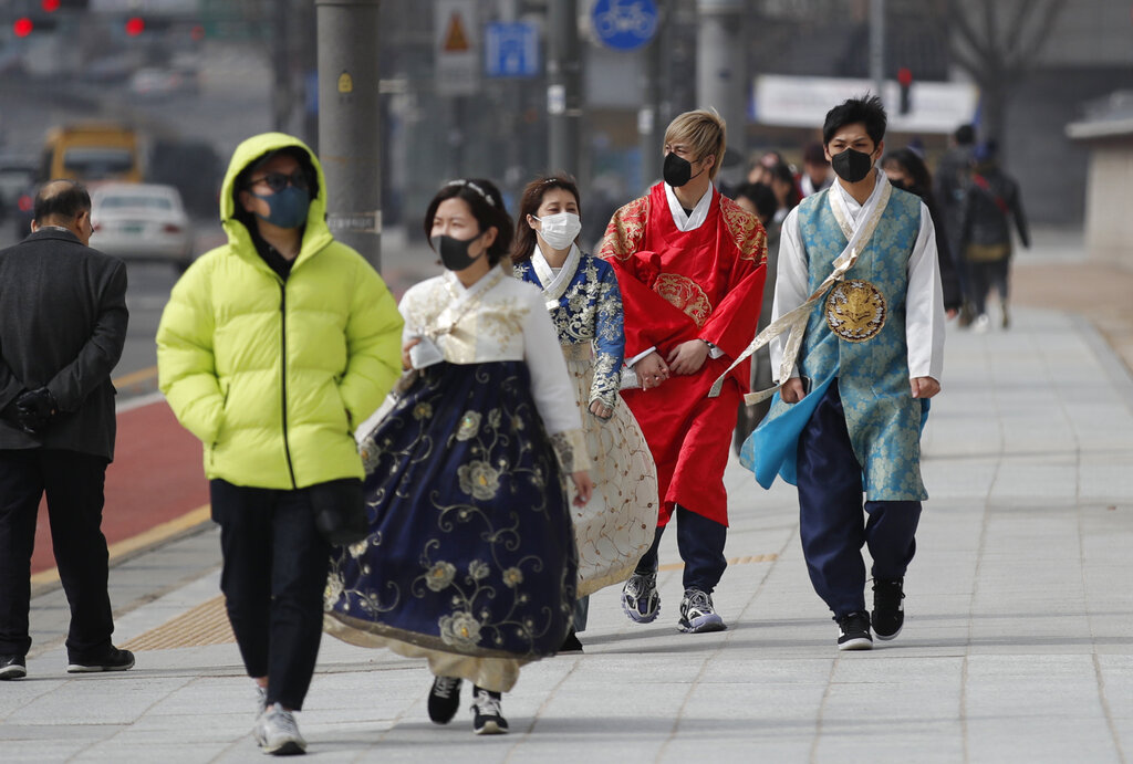 Visitors wearing face masks walk near the Gwanghwamun, the main gate of the 14th-century Gyeongbok Palace, and one of South Korea's well-known landmarks, in Seoul, South Korea, Saturday