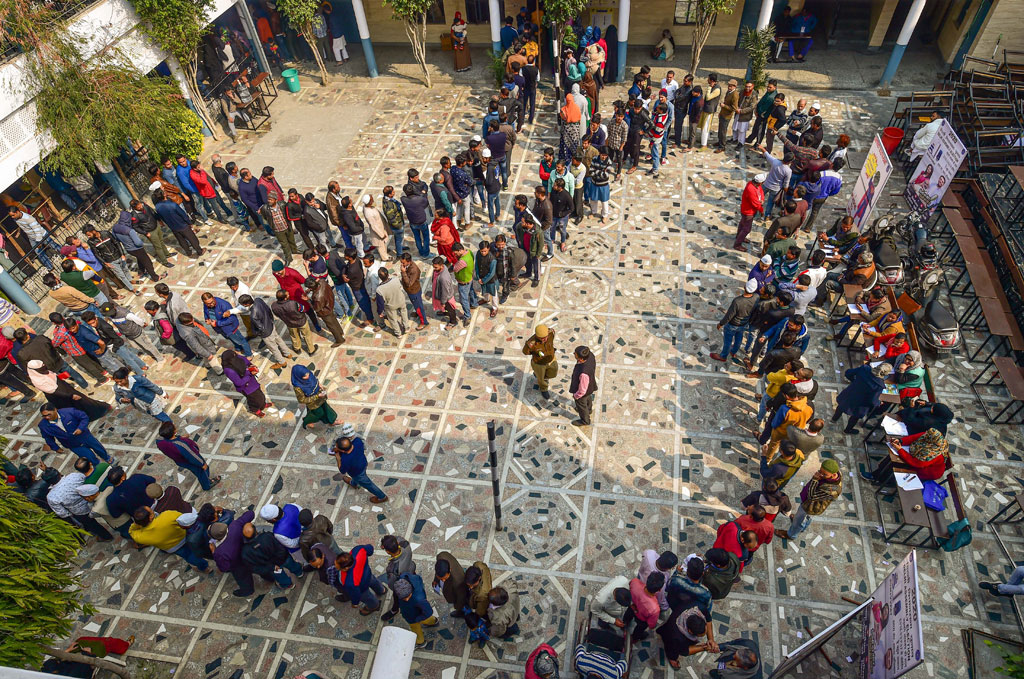 People wait in queues to cast their votes at Shaheen Public School polling station in the Shaheen Bagh area, which has been witnessing a peaceful protest against the Citizenship Act for several weeks, during the Delhi Assembly elections, in New Delhi, on Saturday