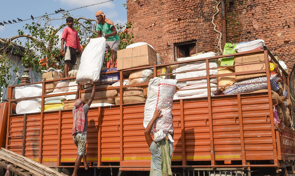 Labourers load goods on a truck at Burrabazar during the fourth phase of Covid-19 lockdown in Calcutta on Friday