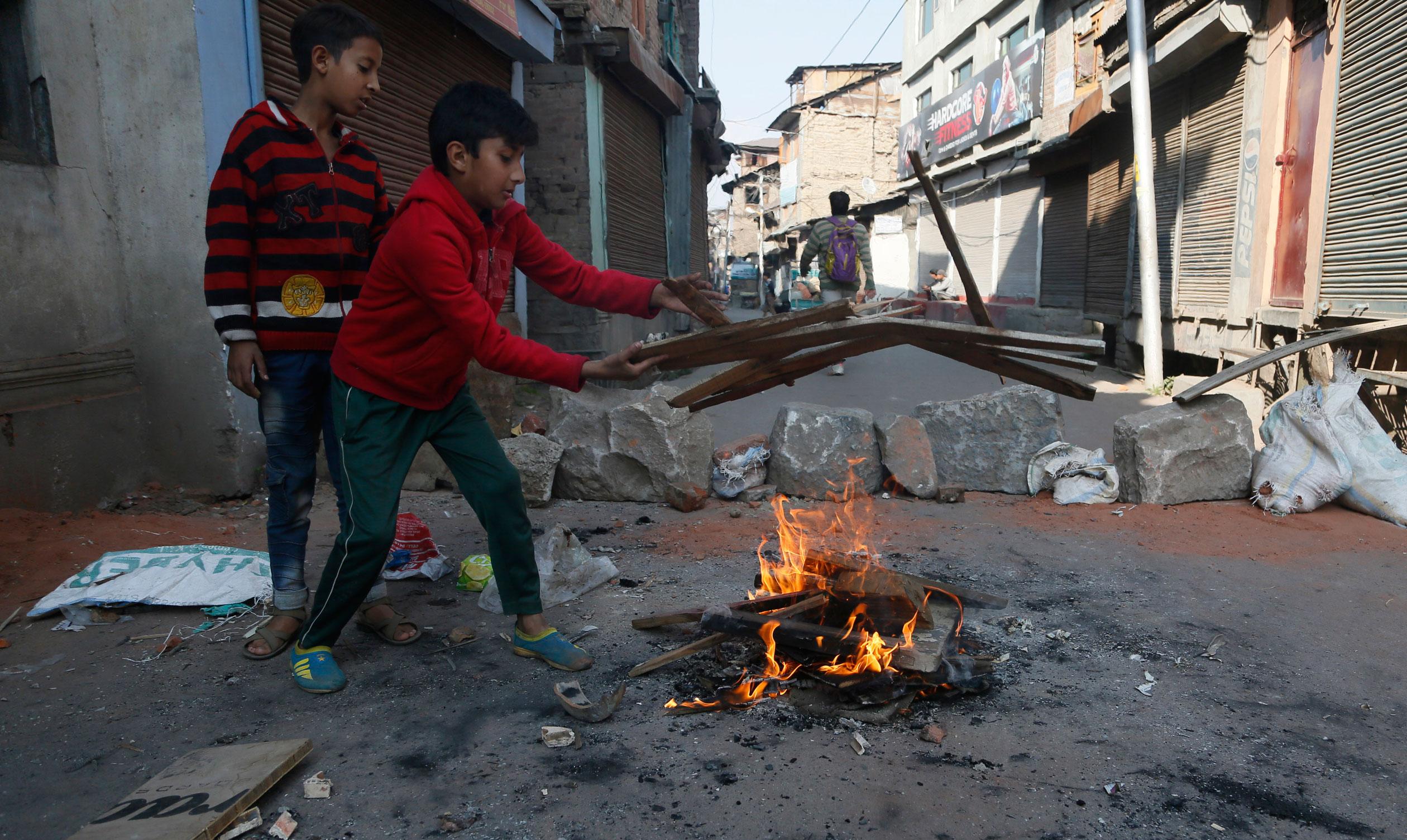 Kashmiri boys add wood to burn near a barricade in downtown Srinagar on October 31, 2019.