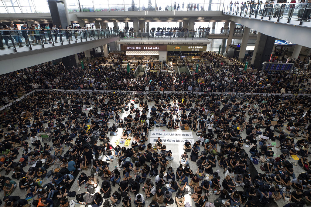 Protesters surround banners that read 'Those charge to the street on today is brave!,' center top, and 'Release all the detainees!' during a sit-in rally at the arrival hall of the Hong Kong International airport on August 12.