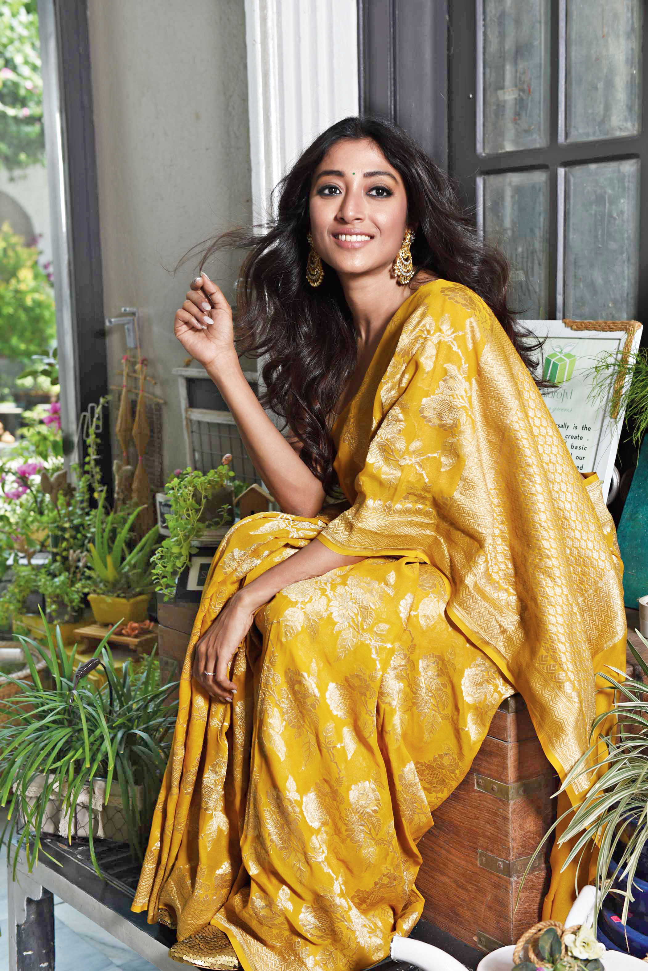 """Sultry simplicity defines this look. Paoli looked resplendent in a handwoven georgette karwa sari made gorgeous with bel and foliage motifs. """"It's lightweight yet the weave is rich because of the use of both silver and gold at the same time. The fabric is comfortable to be worn in this weather. The bride can wear it for one of her main functions,"""" said Pinki. Winged, kohl eyes, nude lips, small bindi, chaandbaali earrings and casual hair add to the look. """"I have worn georgette Benarasi before. The fabric is light on the skin. I like lightweight fabrics for summers and this is perfect. It's a very versatile colour… something both the bride and the bride's mom can wear. While the bride's mom can wear it during the evening, the bride can wear it for her gaaye holud. Fantastic!"""" said Paoli."""