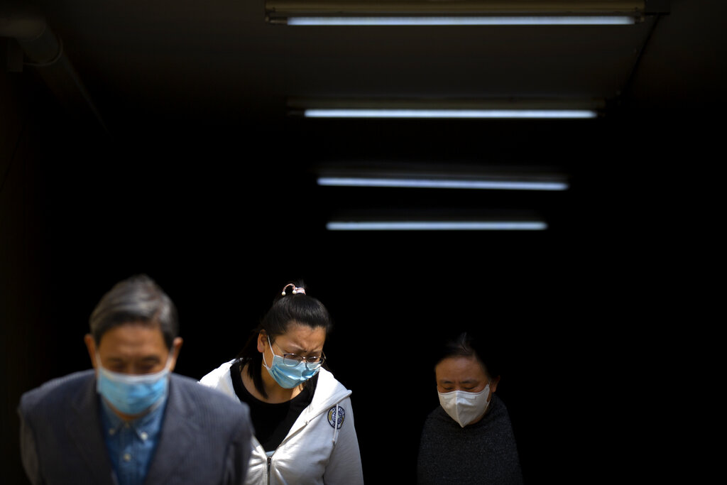 People wear face masks as they exit a subway station in Beijing, Tuesday, April 7, 2020. China on Tuesday reported no new deaths from the coronarivus over the past 24 hours and just 32 new cases, all from people who returned from overseas