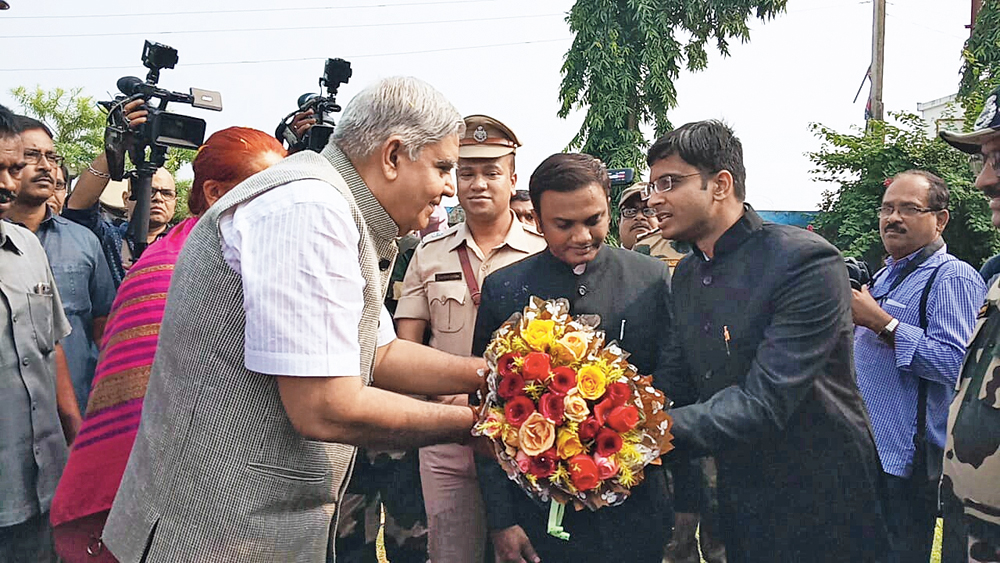 A state administration official welcomes Dhankhar in Dhamakhali with a bouquet on Tuesday