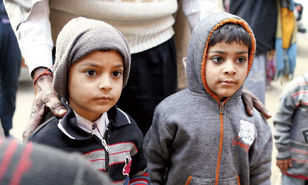 Saahil, 5, (left) and Samar, 6, watch the funeral procession of their father Mahesh Yadav, holding a toy each, in Tudihar village near Allahabad.