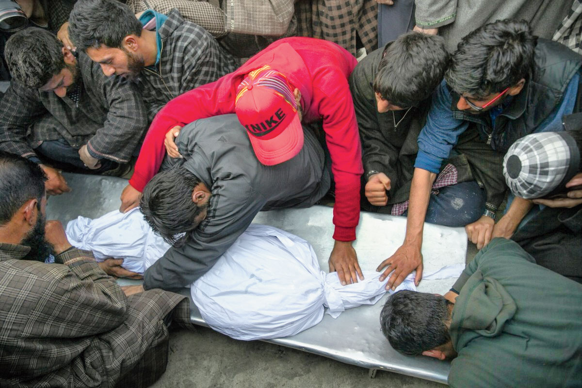 Villagers grieve near the body of an 11-year-old boy, Aatif Mir, in north of Srinagar, on March 22, 2019.