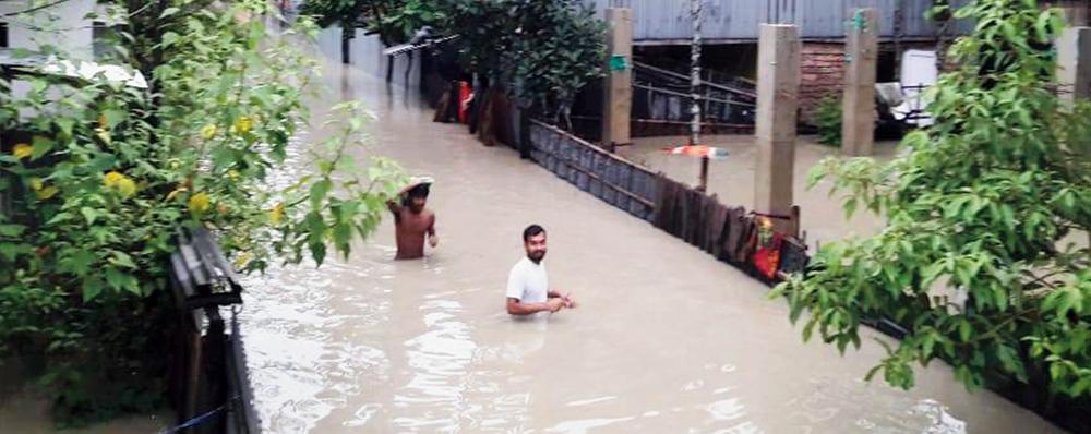 Two men trudge through waist-deep water in Alipurduar on Wednesday