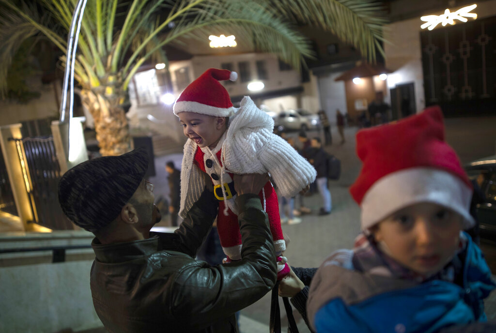 A Palestinian Christian man plays with his baby as they wait for the Christmas Mass outside the Holy Family Catholic Church in Gaza City, Tuesday, Dec. 24, 2019.