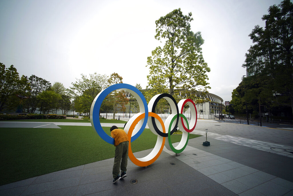 A child plays at the Olympic rings in front of the New National Stadium in Tokyo.