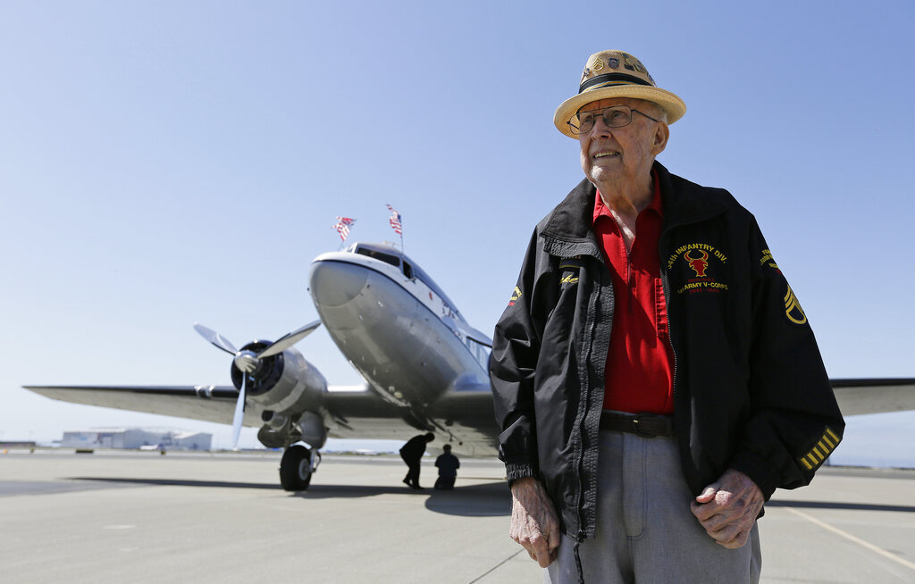 In this photo taken April 29, 2019, D-Day veteran Jake Larson poses before going for a ride in the The Spirit of Benovia World War II-era aircraft in Oakland, California. Both Larson and the former C-53 Skytrooper transport plane plan to be in Normandy and take part in events for the 75th anniversary of D-Day. The plane takes its name after a winery in Sonoma County.